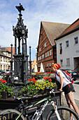 Female cyclist refreshing at fountain Roehrenbrunnen, Leutershausen, Altmuehltal cycle trail, Bavaria, Germany