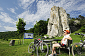 Female cyclist resting near Burgstein, Dollnstein, Altmuehltal cycle trail, Altmuehltal natural park, Bavaria, Germany
