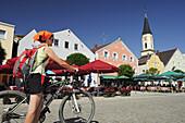 Woman with bicycle at square Ludwigsplatz, Kelheim, Altmuehltal cycle trail, Bavaria, Germany