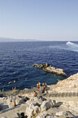 Young men swimming in the sea and jumping from rocks, Hydra, Hydra island, Mediterranean Sea, Greece, Europe