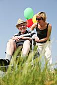 Woman wheeling senior man in a wheelchair, lake Kulkwitzer See, Leipzig, Saxony, Germany