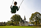 Woman swinging, German Allotment Gardener`s Museum, Leipzig, Saxony, Germany