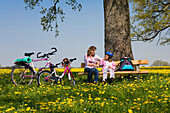 Mother and daughter resting while cycle tour, Upper Bavaria, Germany