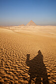 Shadow of a tourist on a camel and the pyramids of Giza, Cairo, Egypt, Africa