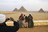 Tourist and local men in front of the pyramids of Giza, Cairo, Egypt, Africa