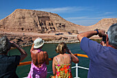 Tourists on a ship photographing the temple of Rameses II., Abu Simbel, Egypt, Africa