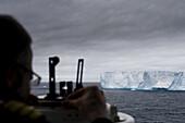 MS Deutschland (Deilmann Cruises) Chief Mate Elmar Mühlebach calculates Antarctic iceberg size with sextant, South Shetland Islands, Antarctica