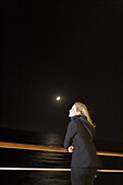 Woman at railing of cruiseship MS Deutschland (Deilmann Cruises) at full moon, South Atlantic Ocean, South America, America