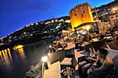 Cafe near the tower of Kizil Kule in the harbourin the evening, Alanya, south coast, Anatolia, Turkey