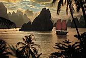Junk in front of limestone formation at sunset, Halong Bay, Vietnam, Asia