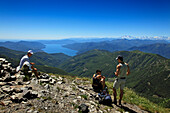 Hikers having a rest at the mountain top of Monte Tamaro, view to Lago Maggiore, hike in the mountains to Monte Tamaro, Ticino, Switzerland