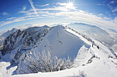 Backcountry skier standing on the edge of a ridge at Rotwand, Rotwand, Spitzing area, Bavarian Pre-Alps, Bavarian Alps range, Upper Bavaria, Bavaria, Germany