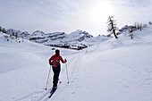 Woman backcountry skiing, ascending towards alpine hut, Fanes-Sennes mountain range in the background, Fanes-Sennes natural park, UNESCO World Heritage Site, Dolomites, South Tyrol, Italy