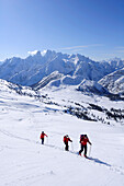 Three people backcountry skiing, ascending to Duerrenstein, Cristallo mountain range in background, Duerrenstein, Fanes-Sennes natural park, UNESCO World Heritage Site, Dolomites, South Tyrol, Italy