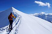 Woman backcountry skiing, ascending mountain on snow-covered ridge, Kreuzjoechl, Tuxer Alpen range, Tyrol, Austria