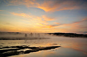 Pre-dawn skies reflected in the Yellowstone River with morning fog