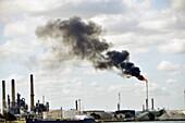 Factory smokestacks along St  Clair River Michigan USA create air pollution