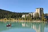 Couple in canoe in front of the hotel Castle Lake Louise, Banff National Park, Rocky Mountains, Alberta, Canada
