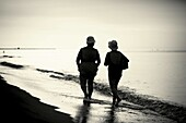 Two women walking along the seashore  Vacation days  Backlit