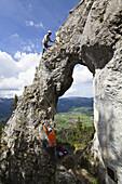 Climbers on a rocky window at Breitenstein moutain near Fischbachau, Wendelstein Mountain Range, Alps, Upper Bavaria, Germany