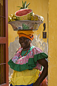 Woman in colorful costume with bowl of fruit on head, Cartagena, Bolivar, Colombia