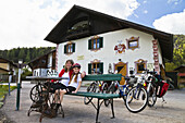 Mother and daughter sitting on a bench, Isar Cycle Route, Scharnitz, Tyrol, Austria