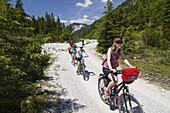 Families cycling along Isar Cycle Route, Hinterau Valley, Karwendel range, Tyrol, Austria