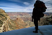 Grand Canyon National Park - Martha Gruelle backpacking in snow near the top of the Bright Angel Trail in the Grand Canyon  Temperatures can be as much as 30 degrees F warmer at the bottom of the canyon  MR Copyright © Jim West