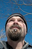 Close-up of a hiker´s beard covered with ice on the side of a hiking trail in the White Mountain National Forest, New Hampshire USA  Note: Weather temp near zero