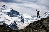 Young woman jumping in Gornetgrat glacier  Switzerland