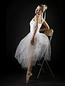 Young woman ballet dancer in white tu-tu dress