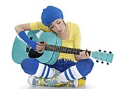 Young woman sitting on the floor and playing the guitar  Isolated on white background