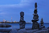 Stone human figures at night over Toronto city view on a shore of lake Ontario Inukshuk Inuit culture Spiritual symbol Atmospheric dramatic nighttime scenery