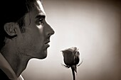 Portrait of a young handsome man with a rose sepia toned image