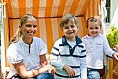Mother and two children sitting in roofed wicker beach chair, Hamburg, Germany