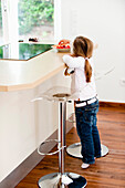 Girl eating strawberries in kitchen, Hamburg, Germany