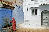 Moroccan woman taking water from a fountain, Chefchaouen, Morocco