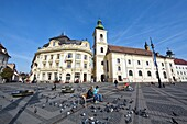 Sibiu, Hermannstadt in Transylvania, Piata Mare with town hall and roman catholic cathedral of the german saxon minority  Locals are feeding pigeons Sunday morning  Europe, Eastern Europe, Romania, Sibiu, September 2009
