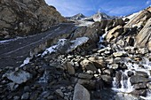 The glacier Simonykees in the National Park Hohe Tauern is retreating rapidly  the glacier snout is flat and new roche moutonnee are distinguishable by the fresh reddish color  A creek is flowing out of the snout of the glacier  Ablation and accumulation