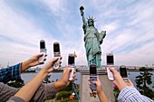 Visitors to copy of Statue of Liberty in Odaiba Tokyo use mobile phones to take photographs