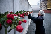 Woman placing red rose on Berlin Wall to commemorate victims killed during escape attempts from East Germany