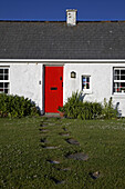 red painted door and footpath leading to cottage in former fishing village of kearney on the irish sea coast of the ards peninsula county down northern ireland uk
