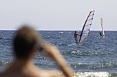 man on the beach takes a photograph of two windsurfers off El Medano beach Tenerife Canary Islands Spain