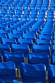 rows of empty blue seats at an outdoor stadium