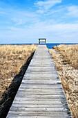 Old wood walkway on sand dune overlooking water in Sandwich Cape Cod