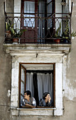 Two women look from a window in Porto Oporto in northern Portugal