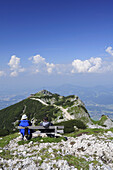 Two hikers sitting on a bench and looking towards Geiereck, Salzburger Hochthron, Untersberg, Berchtesgaden mountain range, Berchtesgaden, Upper Bavaria, Bavaria, Germany