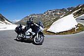 Biker driving on a serpentine mountain pass, snow remains in the background, Timmeljoch, Ötztal, Tirol, Österreich