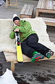 Skier laying on a sunlounger, embracing skis, Flims, Canton of Grisons, Switzerland