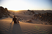 Woman sitting on a dune at sunset, Sudan, Africa